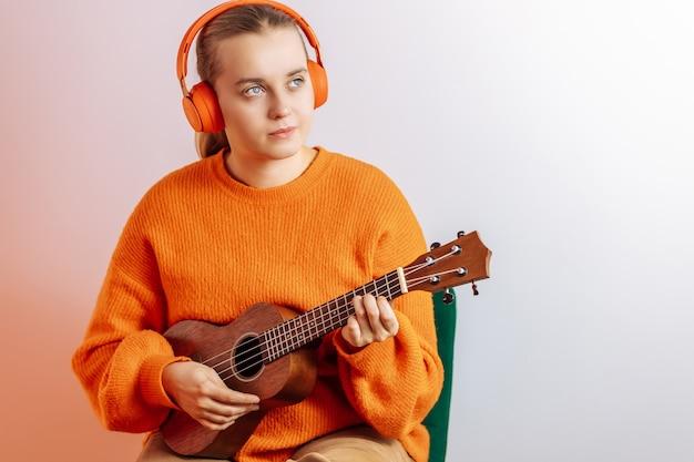 Ein mädchen in einem orangefarbenen pullover und kopfhörern spielt eine ukulele auf hellem hintergrund