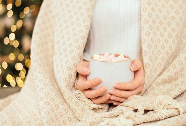 Ein mädchen in einem plaid in einem gestrickten weißen wollpullover hält eine tasse mit heißer schokolade oder kaffee mit marshmallows.