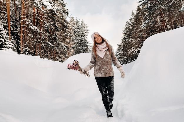 Ein mädchen in einem pullover im winter mit einem blumenstrauß in den händen steht zwischen großen schneeverwehungen.