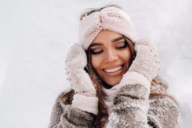 Ein mädchen in einem pullover und fäustlinge im winter steht auf einem schneebedeckten hintergrund.