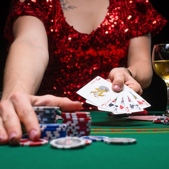 Ein mädchen in einem roten abendkleid spielt poker in einem nachtkasino