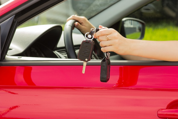 Ein mädchen in einem roten auto demonstriert die schlüssel zu einem neuen auto, das konzept des kaufens eines fahrzeugs