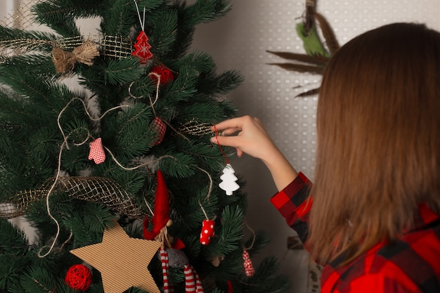 Ein mädchen in einem roten hemd in einem käfig schmückt einen weihnachtsbaum, blick von hinten