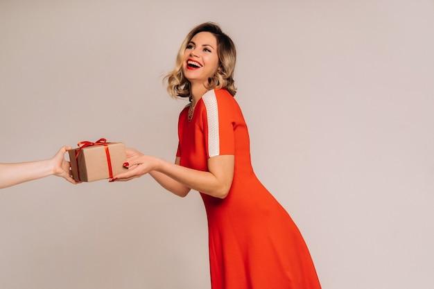 Ein mädchen in einem roten kleid erhält ein geschenk in ihren händen auf einem grauen hintergrund.