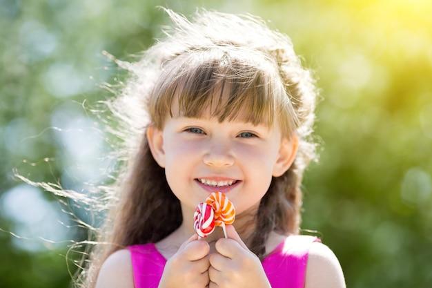 Ein mädchen in einem roten kleid mit bonbons in ihren händen.