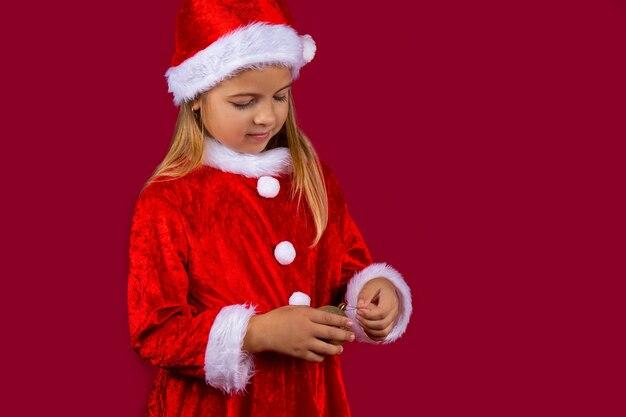 Ein mädchen in einem roten kleid und einer weihnachtsmütze, die ein weihnachtsbaumspielzeug hält. urlaubskonzept.