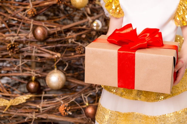 Ein mädchen in einem schicken kleid steht mit einem neujahrsgeschenk in den händen vor dem hintergrund