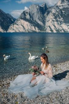 Ein mädchen in einem schicken weißen kleid sitzt am ufer des gardasees. eine frau wird vor dem hintergrund eines berges und eines sees in italien fotografiert. torbole.