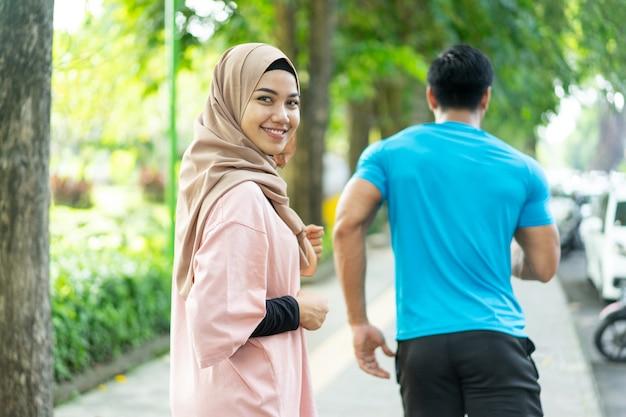 Ein mädchen in einem schleierlächeln schaut in die kamera, wenn sie zusammen joggen, wenn sie im freien im park trainieren