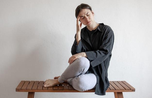 Ein mädchen in einem schwarzen hemd sitzt auf einer bank und leidet unter geistigen oder körperlichen schmerzen.
