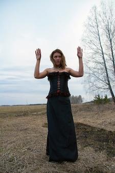 Ein mädchen in einem schwarzen kleid im wald. das mädchen ist eine hexe in einem schwarzen korsett. dunkler wald mit trockenen zweigen