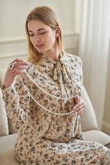 Ein mädchen in einem sommerkleid hält eine perlenkette in den händen