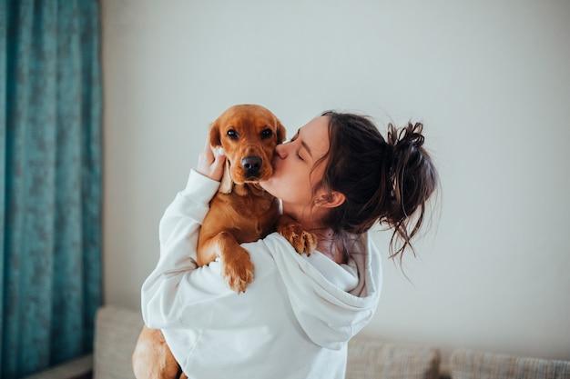 Ein mädchen in einem weißen hoodie küsst einen hund