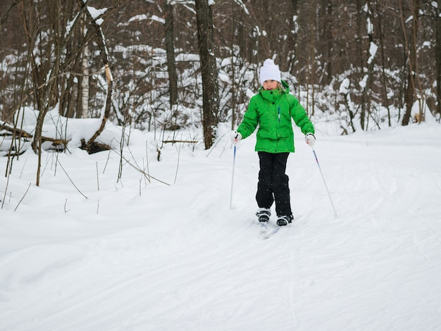 Ein mädchen in einem weißen hut und einer grünen jacke, die übungen auf skiern machen.