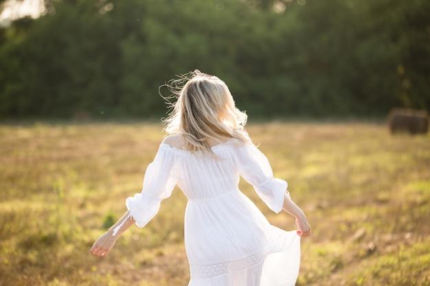 Ein mädchen in einem weißen kleid mit wallendem haar auf dem feld