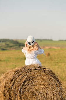 Ein mädchen in einem weißen kleid sitzt auf einem heuhaufen
