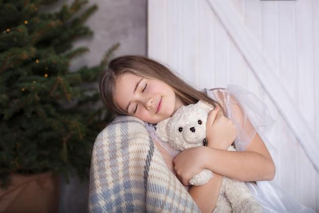 Ein mädchen in einem weißen kleid sitzt auf einem stuhl mit einem teddybären und träumen. gemütliches zu hause. zimmer im öko-stil im einklang mit der natur. das mädchen schlief ein und träumte. träum süß. mädchen in einem traum.