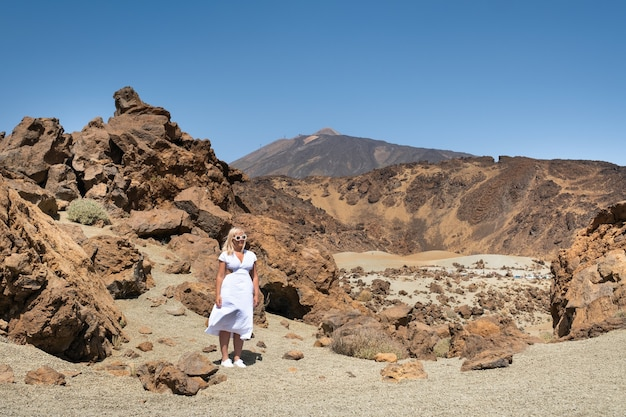 Ein mädchen in einem weißen kleid steht im krater des teide-vulkans. teneriffa, kanarische inseln.