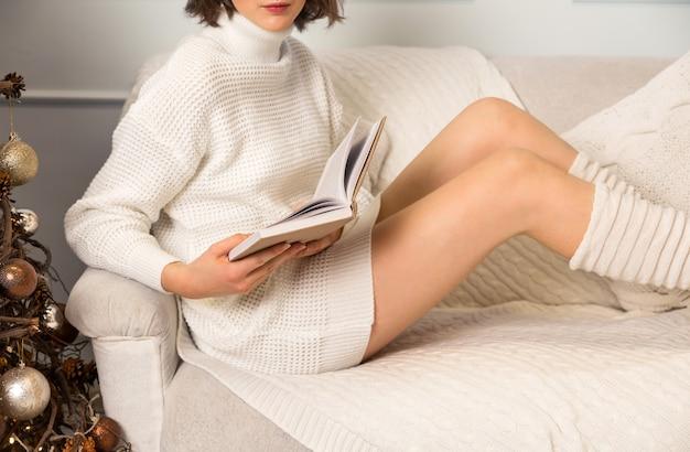 Ein mädchen in einem weißen pullover und leggings sitzt auf der couch und liest ein buch