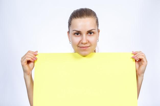 Ein mädchen in einem weißen t-shirt hält ein gelbes, leeres großes blatt banner.