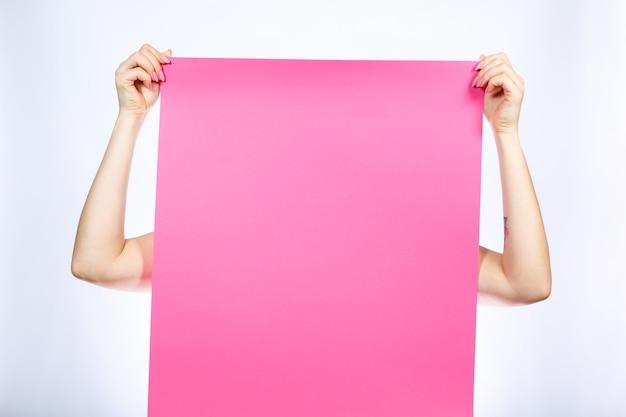 Ein mädchen in einem weißen t-shirt hält ein rosa leeres großes banner in ihren händen.