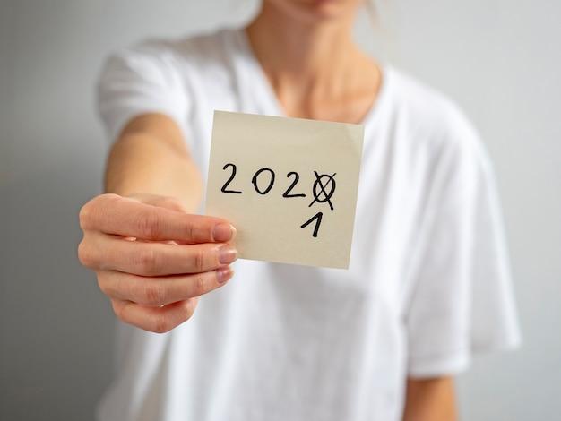 Ein mädchen in einem weißen t-shirt hält einen aufkleber mit der aufschrift 2021 in der hand. das konzept der ankunft des neuen jahres. konzentrieren sie sich auf den aufkleber
