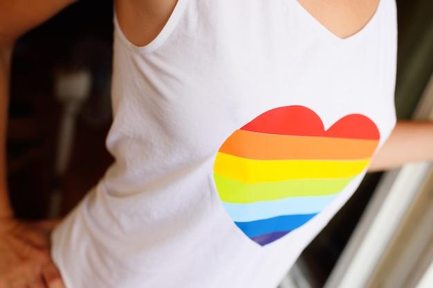 Ein mädchen in einem weißen t-shirt mit einem bild eines herzens mit einem regenbogen. das konzept von lgbt