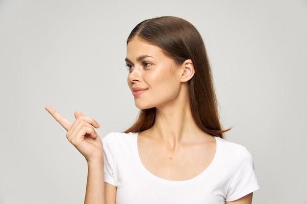Ein mädchen in einem weißen t-shirt zeigt zur seite und dreht den kopf