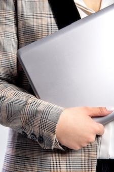 Ein mädchen in einer karierten jacke hält einen grauen laptop in den händen