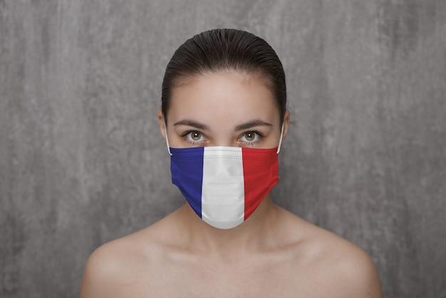 Ein mädchen in einer maske im gesicht mit der flagge frankreichs