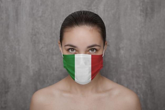 Ein mädchen in einer maske im gesicht mit der flagge italiens