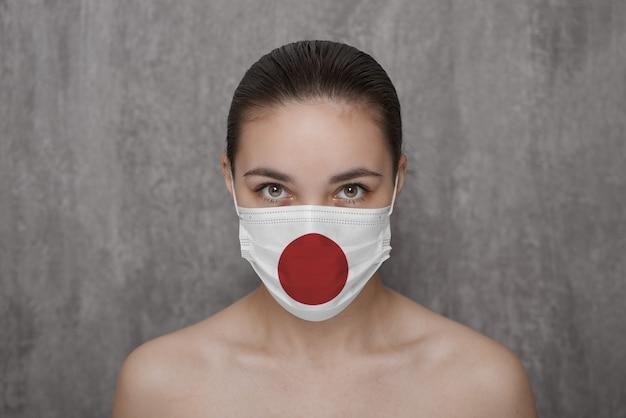 Ein mädchen in einer maske im gesicht mit der flagge japans