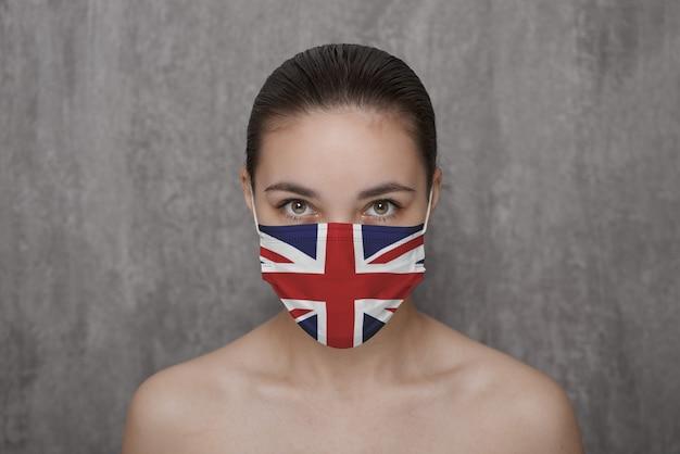 Ein mädchen in einer maske im gesicht mit einer britischen flagge