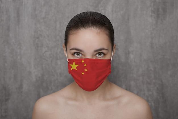 Ein mädchen in einer maske im gesicht mit einer chinesischen flagge