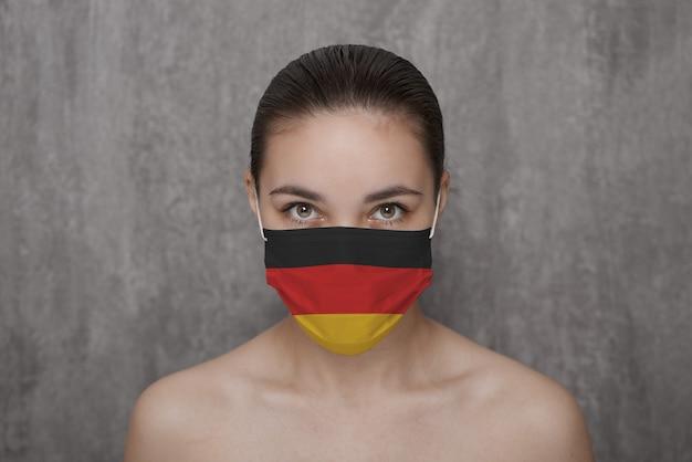 Ein mädchen in einer maske im gesicht mit einer deutschen flagge