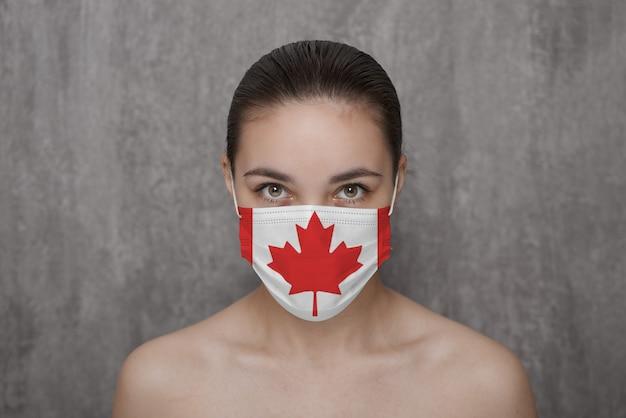 Ein mädchen in einer maske im gesicht mit einer kanadischen flagge