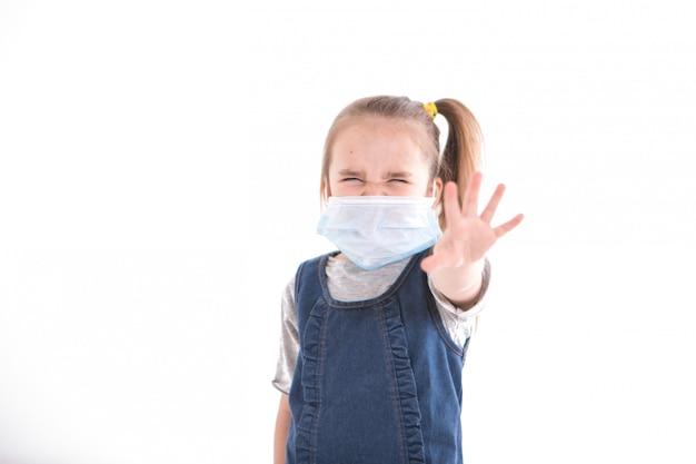 Ein mädchen in einer medizinischen maske sagt, dass die infektion gestoppt werden soll. das kind legte seine hand nach vorne. prävention der krankheit. isoliert auf weißer wand