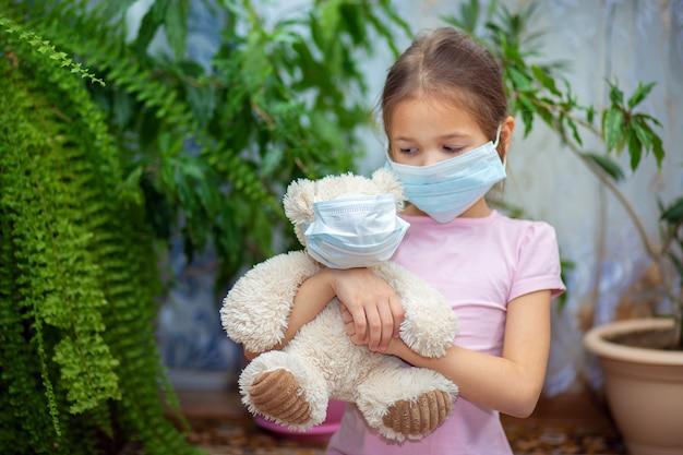 Ein mädchen in einer medizinischen maske sitzt zu hause während einer vieste-epidemie mit ihrem teddybär ebenfalls in einer maske