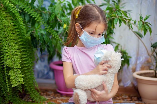 Ein mädchen in einer medizinischen maske spielt zu hause mit ihrem teddybär, der ebenfalls eine maske trägt