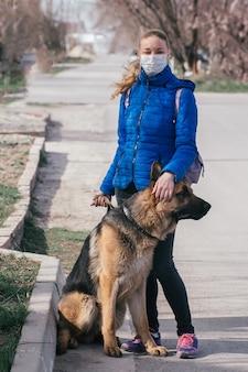 Ein mädchen in einer medizinischen schutzmaske geht mit einem hund auf die straße. freizeit mit einem haustier während der quarantäne. gehen sie mit einem deutschen schäferhund