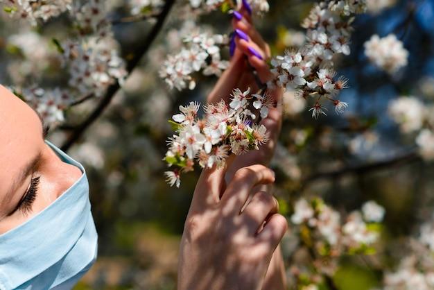 Ein mädchen in einer medizinischen schutzmaske im frühjahr inmitten des blühenden gartens. . frühlingsallergie konzeption