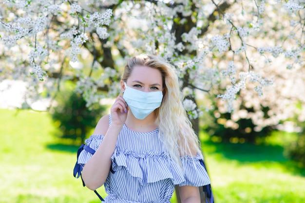 Ein mädchen in einer medizinischen schutzmaske im frühjahr inmitten des blühenden gartens. . frühlingsallergie und covid-konzept.