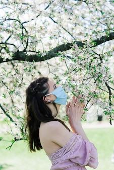 Ein mädchen in einer medizinischen schutzmaske im frühjahr inmitten des blühenden gartens. frühlingsallergie und covid-konzept.