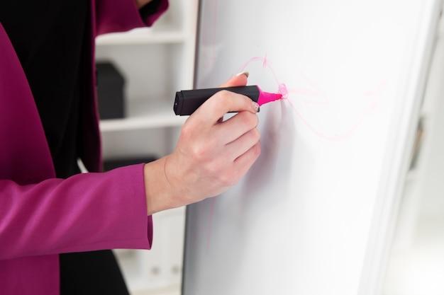 Ein mädchen in einer rosa jacke schreibt mit einem marker an eine tafel
