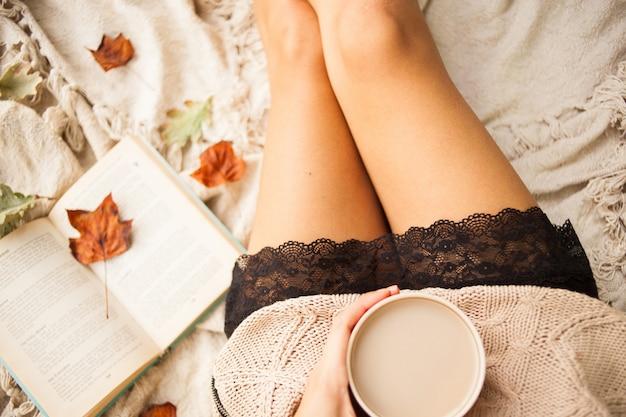 Ein mädchen in einer warmen strickjacke sitzt auf einer beige wollenen decke und hält einen becher heißen kaffee in der hand.