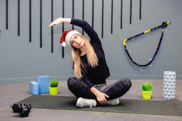 Ein mädchen in einer weihnachtsmannmütze, die fitnessübungen im fitnessstudio macht