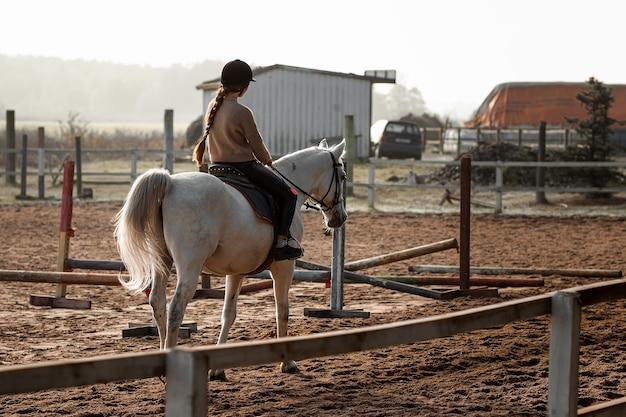 Ein mädchen in form eines jockeys reitet auf einem pferd im hippodrom. reitstunden, reiten.