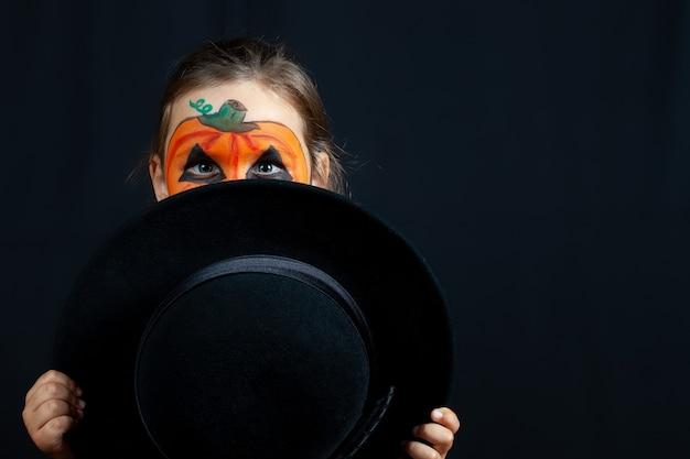 Ein mädchen in kürbis make-up für halloween versteckt sich hinter einem schwarzen hut in ihren händen, isoliert.