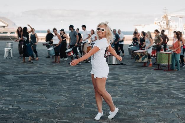 Ein mädchen in weißer kleidung auf dem hintergrund von menschen, die sich in der stadt santa cruz de tenerife am wasser mit fitness beschäftigen. kanarische inseln, spanien
