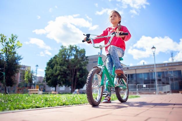 Ein mädchen in zerrissenen jeans fährt fahrrad im park.